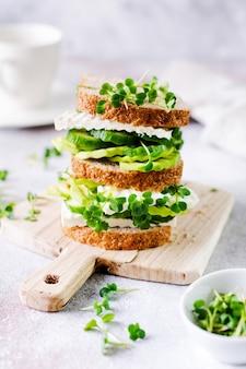 아보카도, 오이, 페타 치즈 샌드위치는 마이크로 그린과 잡곡 빵으로 장식 된 간단한 나무 스탠드에 건강한 아침 식사를 제공합니다. 선택적 초점