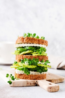 Avocado, cucumber and feta cheese sandwich decorated with micro-greens and multi-grain bread on a simple wooden stand for a healthy breakfast