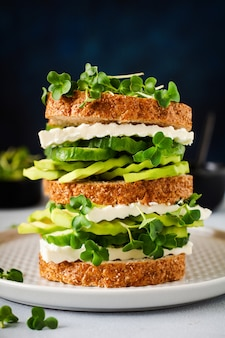 Avocado, cucumber and feta cheese sandwich decorated with microgreens and multigrain bread on a simple wooden stand for a healthy breakfast. selective focus