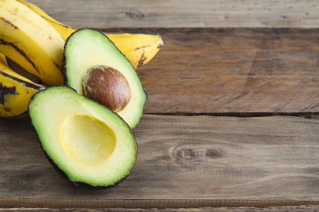 Avocado cut in half and banana on wooden surface. copy space.