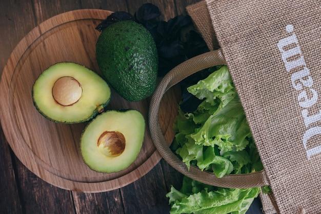 アボカドは木製のテーブル、コリアンダー、バジルをストローバッグの横で半分にカットしました。適切で健康的な栄養、菜食主義の概念。
