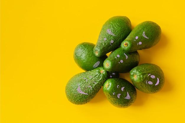 Авокадо смайликов на желтом фоне копией пространства
