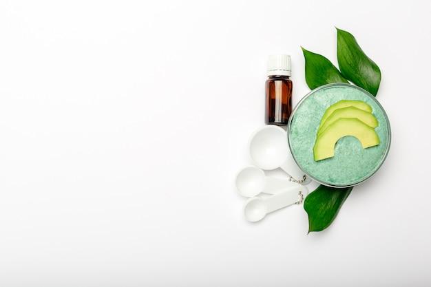 ガラスの瓶に入ったアボカドのフェイスマスク、つぶしたアボカド、エッセンシャルオイル、スプーンから作られた自家製の栄養マスク。 diy自家製化粧品のレシピ、スキンケア。アボカドフラットレイアウトホワイトバックグラウンドコピースペース