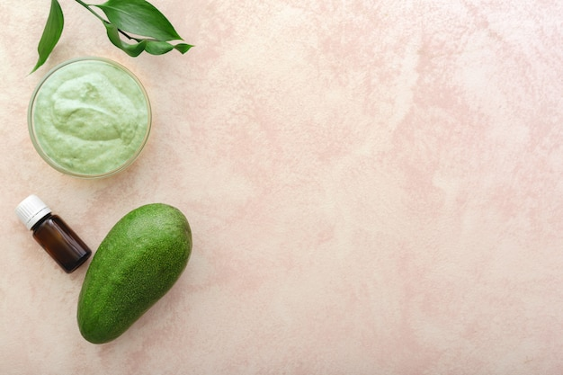 Маска для лица из авокадо в стеклянной банке с листьями и маслом авокадо