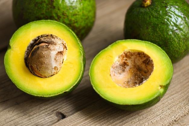 Плоды авокадо и авокадо ломтик на деревянном столе, концепция здорового питания фруктов.