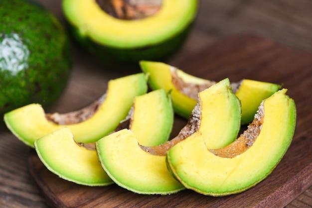 Фрукты авокадо и ломтик авокадо на деревянном