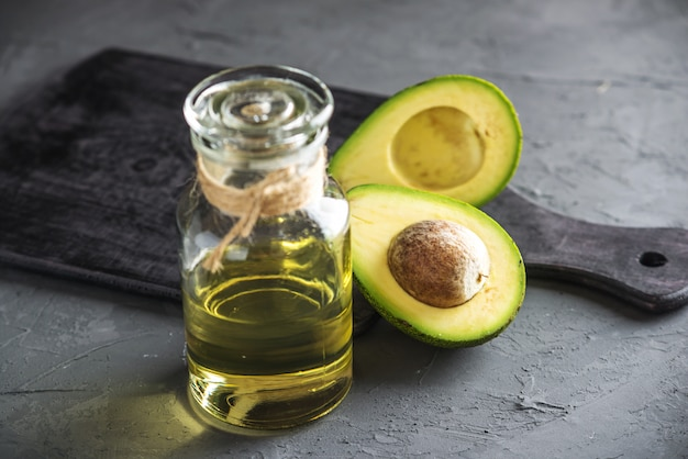 Avocado fruit and oil in glass bottle