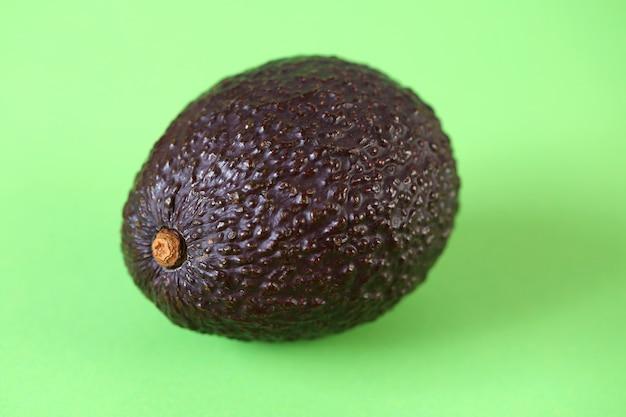 アボカドフルーツ。薄緑色のテーブルに熟したアボカド。便利なダイエット製品。健康的な脂肪。オーガニックバイオフレッシュアボカド