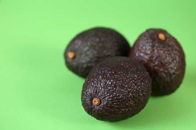 アボカドフルーツ。薄緑色のテーブルに3つの熟したアボカドがセットされています。便利なダイエット製品です。健康的な脂肪。オーガニックバイオフレッシュアボカド