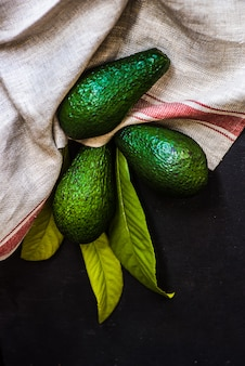 Avocado fruits on dark table