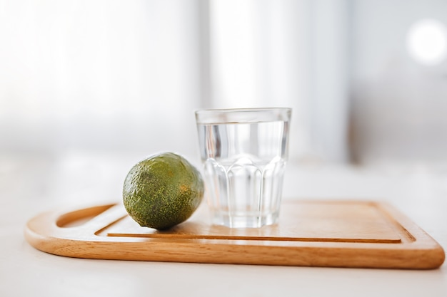 Avocado and a glass of water on a wooden board. health care and diet concept