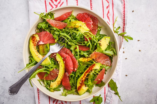 Avocado and grapefruit salad in a white plate on a white background.