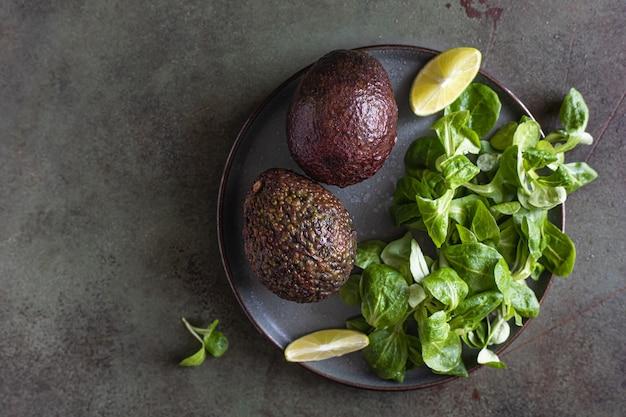 아보카도, 녹색 잎 샐러드, 라임 조각은 녹색 콘크리트 배경에 있습니다. 건강한 지방. 평면도.