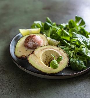 아보카도, 녹색 잎 샐러드, 라임 조각은 녹색 콘크리트 배경에 있습니다. 건강한 지방.