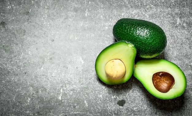 Зеленый авокадо на каменном столе.