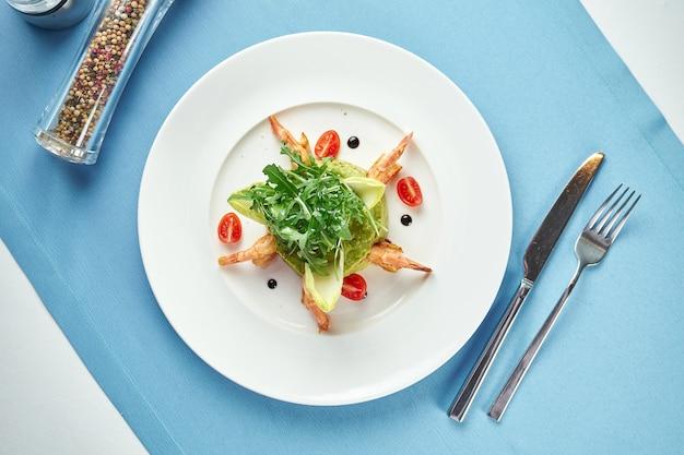 Авокадо гуакамоле с креветками, рукколой и помидорами черри в белой тарелке на синей скатерти. закройте вверх. мексиканская еда