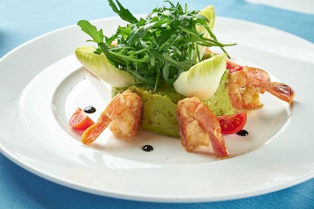 青いテーブルクロスの白いプレートにエビ、ルッコラ、チェリートマトを添えたアボカドワカモレ。閉じる。メキシコ料理