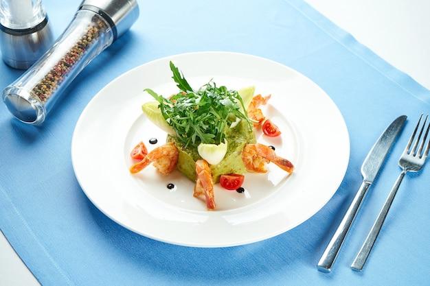 青いテーブルクロスの白いプレートにエビ、ルコラ、チェリートマトを添えたアボカドワカモレ。閉じる。メキシコ料理