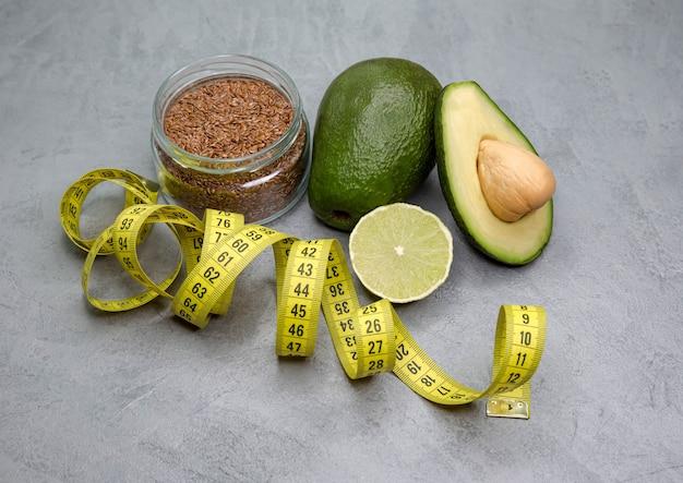Половина авокадо с рулеткой на серой поверхности. веганская сбалансированная диета