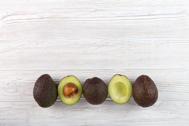 Avocado - halved and whole avocados on white wooden background