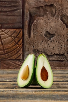 Avocado halves on old wooden and stone tiles. side view.
