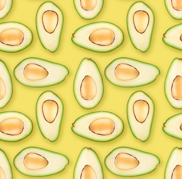 Половинки авокадо на желтом фоне, этот фон бесшовный, вы можете сделать свой собственный аф любого размера