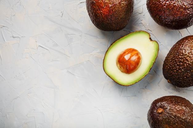 Половинки авокадо с целыми плодами хасса на поверхности серого бетона