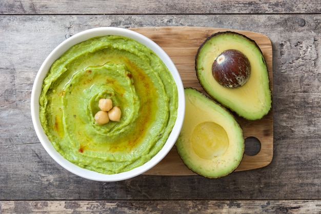 Avocado hummus in bowl wooden table top view