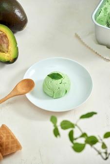 白い皿にアボカドのアイスクリームボール、スプーン