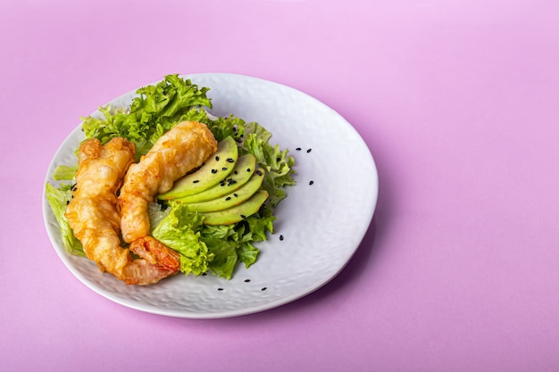 Avocado and king prawns salad on green leaves. festive dinner. healthy eating. on a pink background. copy space.