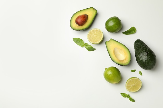 Avocado, lime and basil on white background, space for text