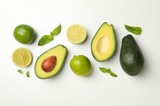 Avocado, lime and basil on white background, top view