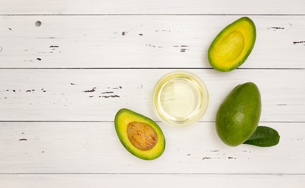 Avocado oil in a glass cup and avocado fruit on a white wooden background, top view, copyspace