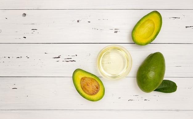 Масло авокадо в стеклянной чашке и фрукты авокадо на белом деревянном фоне, вид сверху, copyspace