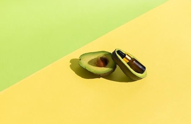아보카도 오일 병은 천연 화장품이라는 개념의 과일 안에 있습니다.