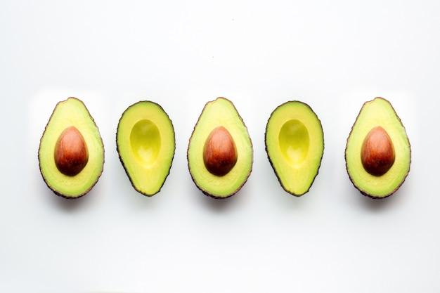 Авокадо на белом фоне. нарезанный авокадо лежит в одну строчку. фрукты разбрасывают на столе