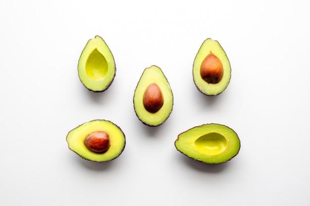 흰색 배경에 아보카도. 아보카도는 사각형으로 늘어서 있습니다. 적절한 영양 성분