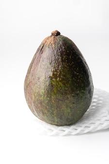 흰색 배경에 고립 된 포장 된 폼 메쉬에 아보카도, 아보카도의 살은 크림 같고 버터 맛이 부드럽습니다. 아보카도에는 영양소, 비타민 및 좋은 지방이 포함되어 있습니다.