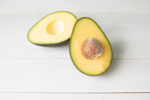 Авокадо на старинном белом столе, концепция здорового питания, овощи и фрукты