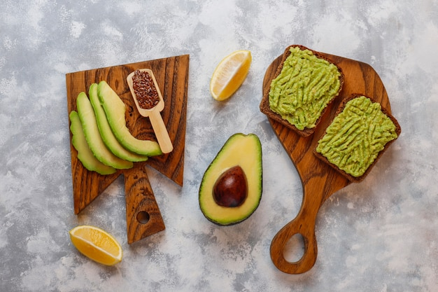 Avocado open toast with avocado slices, lemon, flax seeds, sesame seeds, black bread slices, top view