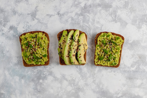 Avocado open toast with avocado slices, lemon, flax seeds, sesame seeds, black bread slices, top view