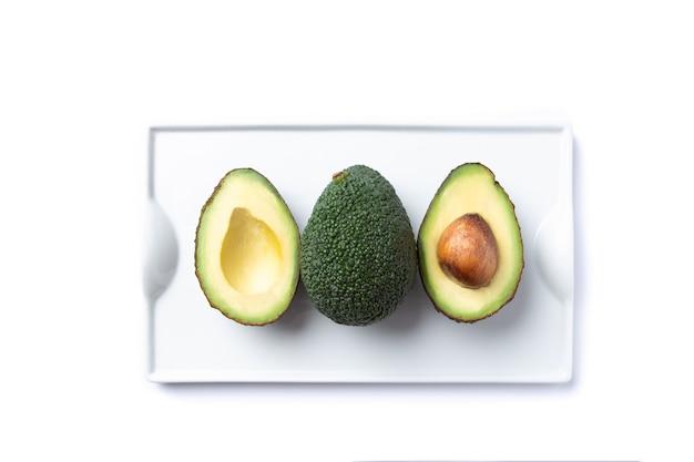 Кусочки авокадо на белой тарелке, изолированные на белом фоне. вид сверху.