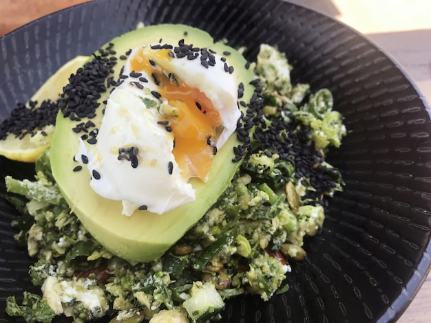 Avocado, poached egg with green salad, healthy vegetarian meal, ketogenic food