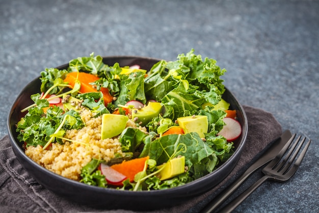 Avocado, quinoa, yam and kale salad in black plate on a dark background.