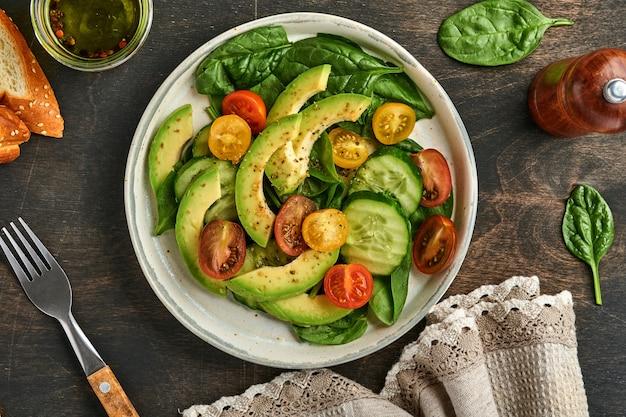 아보카도, 빨간색, 노란색, 검은색 체리 토마토, 시금치, 오이 신선한 샐러드와 향신료 후추, 올리브 오일이 회색 그릇에 담긴 오래된 나무 테이블 배경입니다. 건강 식품 개념입니다. 평면도.