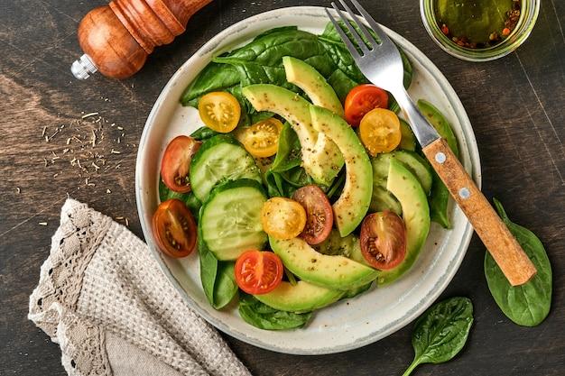 아보카도, 빨간색, 노란색, 검은 색 체리 토마토, 시금치, 오이 신선한 샐러드와 향신료 후추와 올리브 오일 회색 그릇 오래 된 나무 테이블 배경. 건강 식품 개념. 평면도.