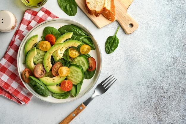 아보카도, 빨강, 노랑, 검정 체리 토마토, 시금치, 오이 신선한 샐러드와 향신료 후추, 올리브 오일을 회색 슬레이트, 돌 또는 콘크리트 배경에 회색 그릇에 담습니다. 건강 식품 개념입니다. 평면도.