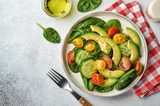 아보카도, 빨간색, 노란색, 검은 색 체리 토마토, 시금치 및 오이 신선한 샐러드와 향신료 후추와 올리브 오일이 회색 슬레이트, 돌 또는 콘크리트 배경에 회색 그릇에 있습니다. 건강 식품 개념. 평면도.