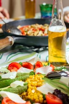 アボカドサラダと背景にメキシコ料理の鍋