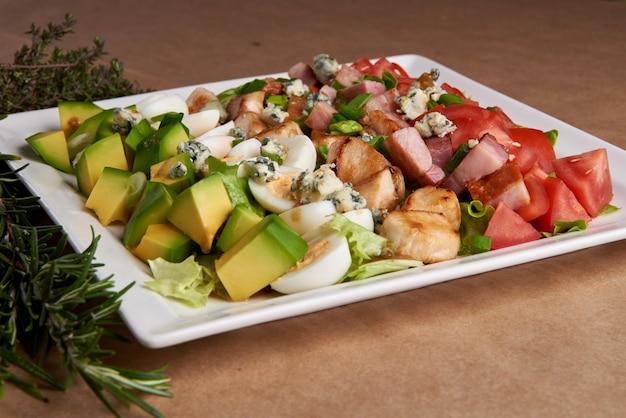 Салат из авокадо, яйцо, курица, бекон, помидоры,